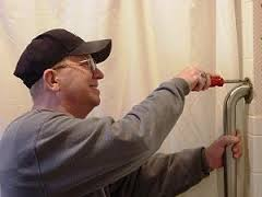 Senior handyman fixing bathroom grab rail