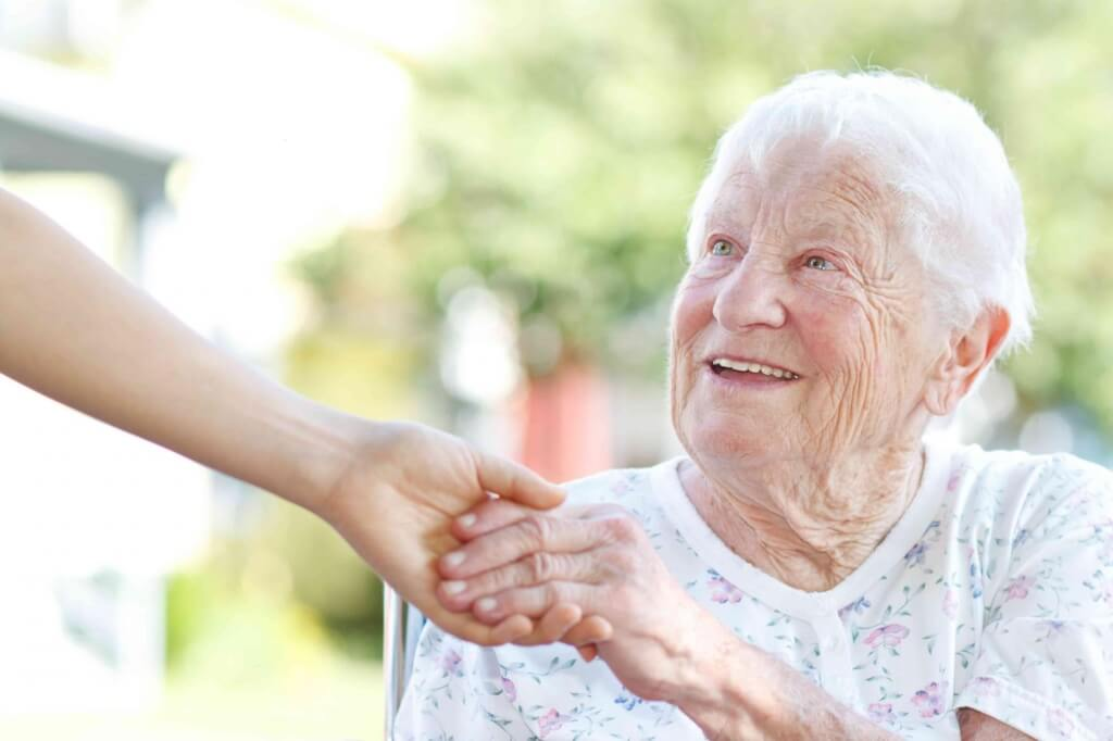 Woman holding the hand of a smiling elderly lady