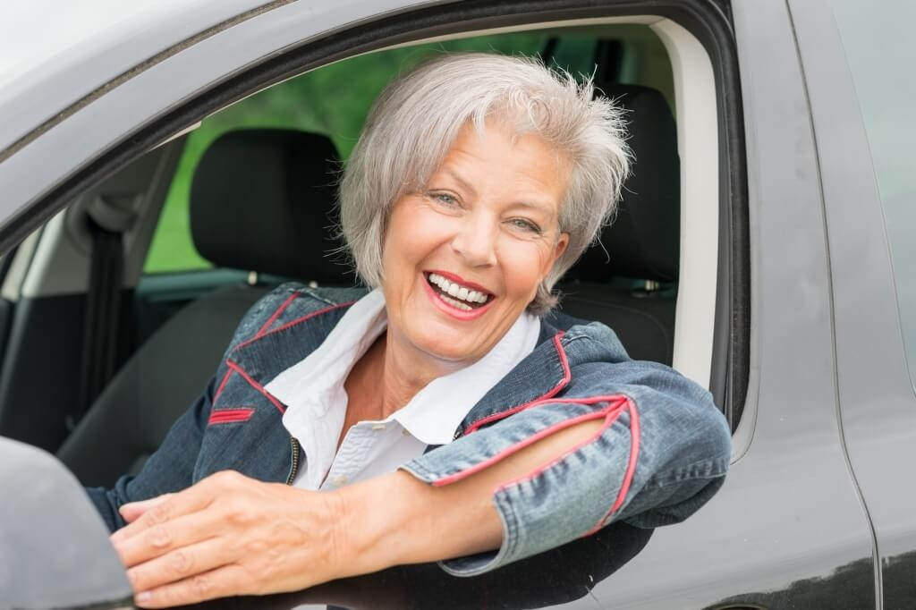 Senior woman driving a car smiling from ear to ear