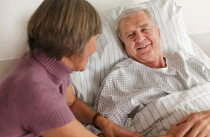 Older woman at the bed side of a senior man