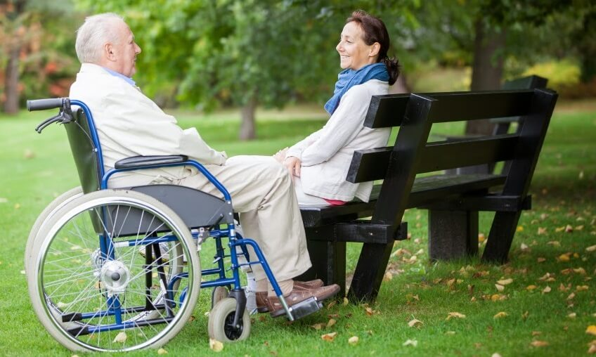 Senior woman spending time with elderly man in a wheelchair in a park