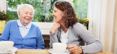 Woman laughing with an elderly lady while drinking tea